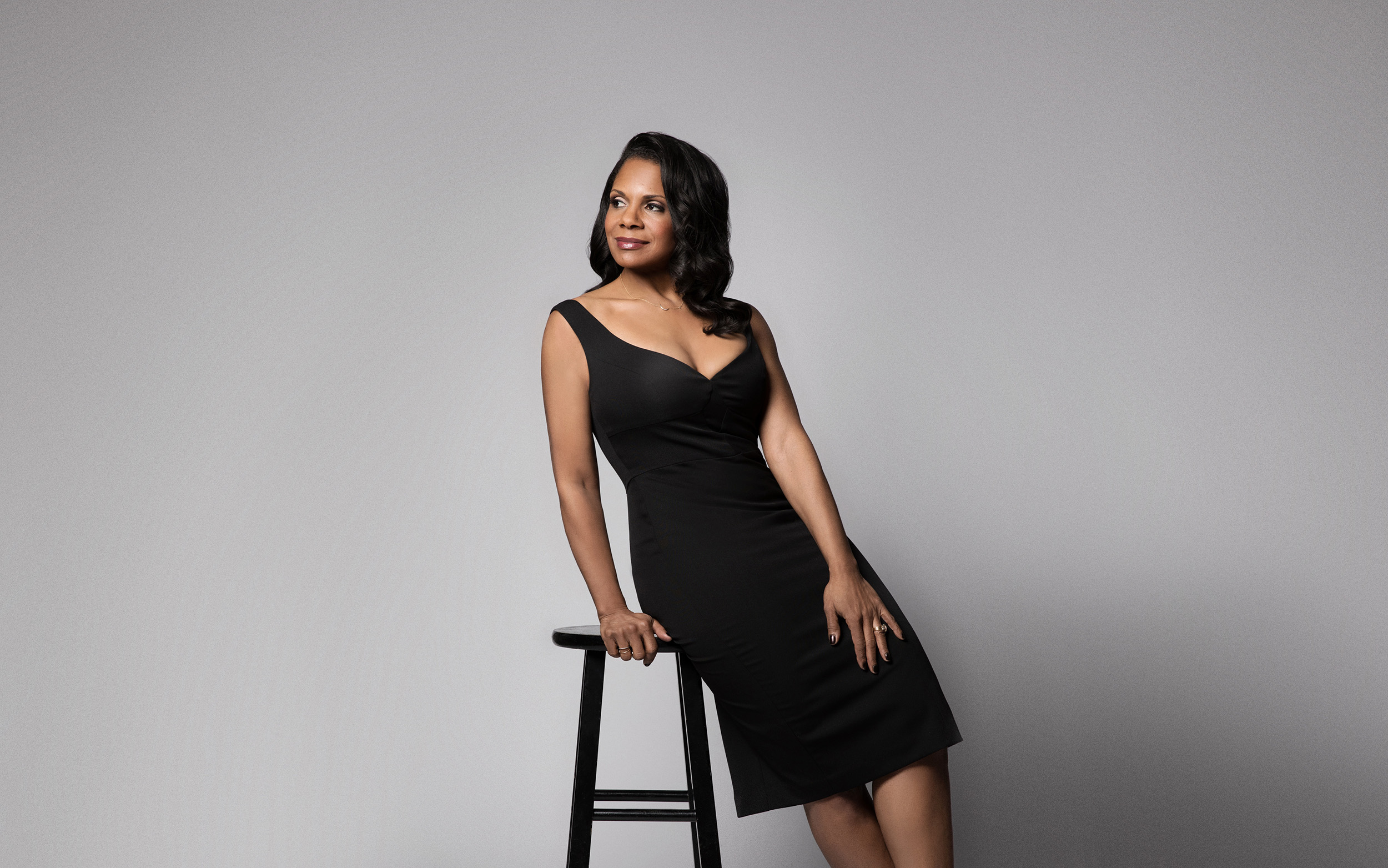 Audra McDonald sits on a stool wearing a form fitting black stress and looking off to the side smiling.
