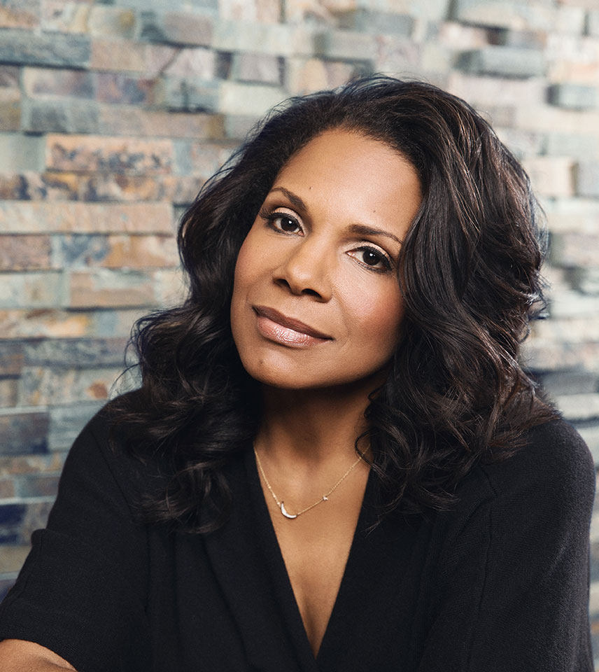 Audra McDonald sits in front of a multi-colored stone wall, wearing a black top and faintly smiling while looking toward the camera.