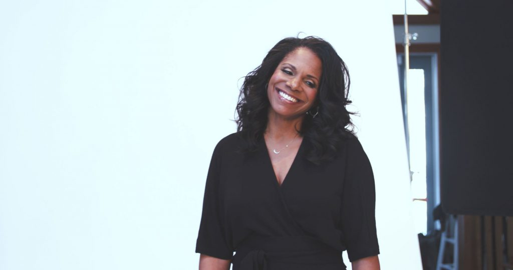 Audra McDonald smiles with her head tilted to the side, posing in front of a white background.