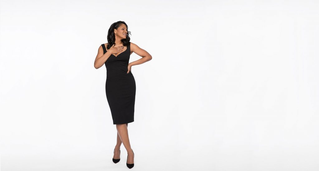 Audra McDonald wears a form-fitting black dress with her head turned to the side with her eyes closed, with one hand on her tip and the other resting against her chest.