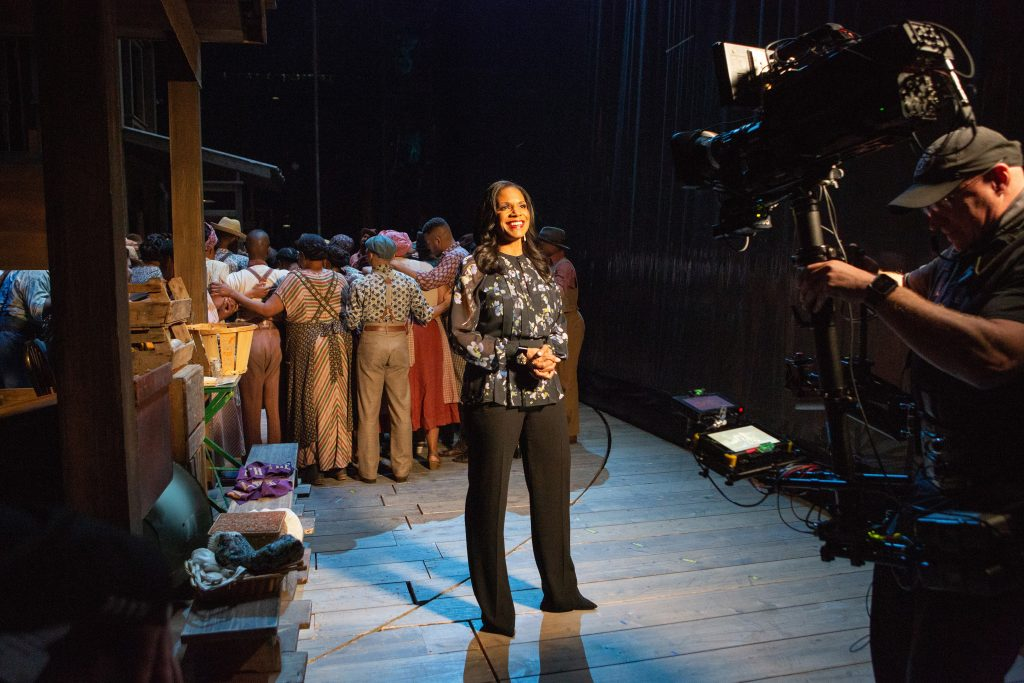 Audra McDonald hosts the Met Opera Live in HD of Porgy and Bess. She stands in front of a camera smiling in front the the cast who are about to go onstage.